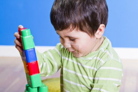 Photo for Brunette Baby playing with bright blocks on wooden room - Royalty Free Image
