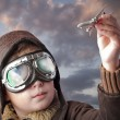 Boy dressed up in pilot outfit, jacket, hat and glasses.