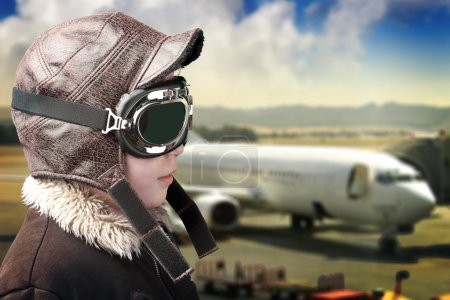 Boy playing with pilot is hat and airport background