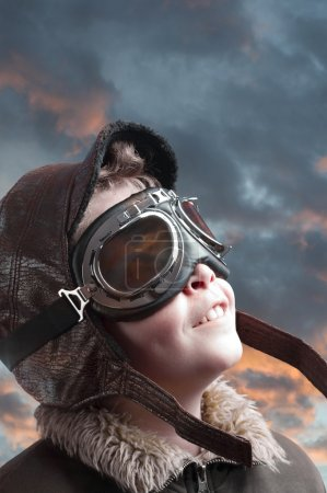 Boy playing with pilot hat and cloudy background