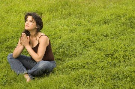 Photo pour Jeune femme assise dans la pose de prière . - image libre de droit