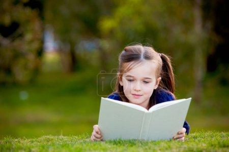 Foto de Una niña está acostada sobre su estómago leyendo sobre la hierba. tiene una mirada de placer en su cara y se ve muy relajada. Hay un poco de negati - Imagen libre de derechos