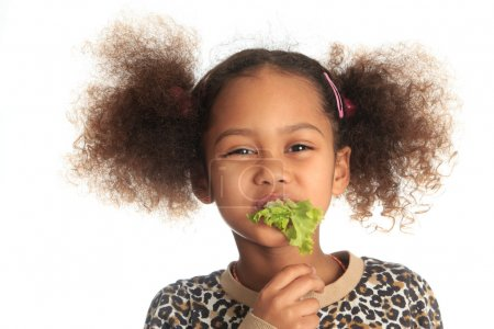 Photo for Beautiful asian child African American Black child eats salad isolated metisse - Royalty Free Image