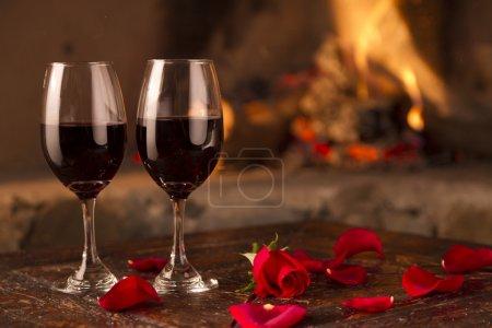 Photo pour Deux mains ayant un romantique toast dans chambre d'hôtel avec fleurs et feu derrière - image libre de droit