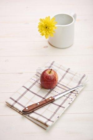 Foto de Manzana roja sobre una mesa blanca, en backgroiund una flor - Imagen libre de derechos