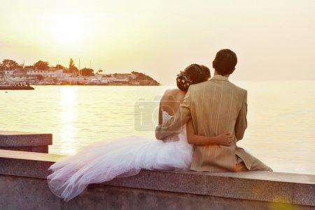 Photo pour Un jeune couple de mariage assis près de la mer - image libre de droit