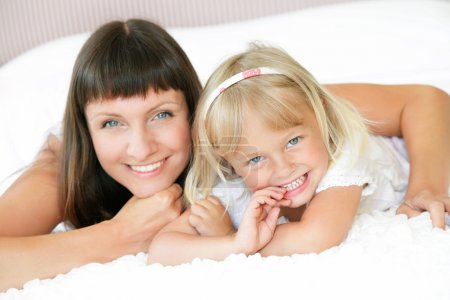 Photo for Mother and daughter posing happily in bed. Shallow DoF. Focus on daughter. - Royalty Free Image