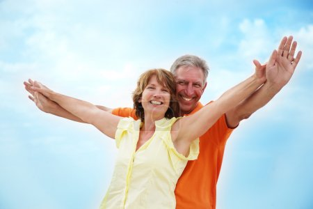 Photo for Mature couple with arms outstretched over a blue sky background. - Royalty Free Image