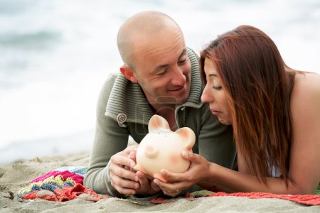 Photo for Young couple holding a piggy bank. - Royalty Free Image