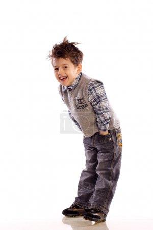 Foto de Niños europeos jóvenes riendo sobre fondo blanco en un suéter de punto y pantalones vaqueros - Imagen libre de derechos