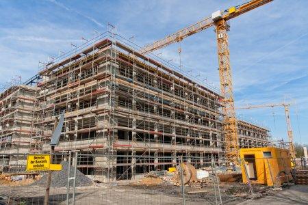 Photo pour Grand chantier avec la construction d'échafaudages, grues à tour jaune et ciel bleu. - image libre de droit