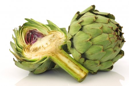 One whole and cut artichoke