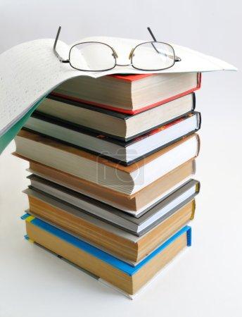 Photo pour Pile de livres avec un cahier et des lunettes (c'est rapide à l'école ) - image libre de droit