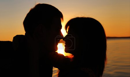 Romantic couple kissing at sunset