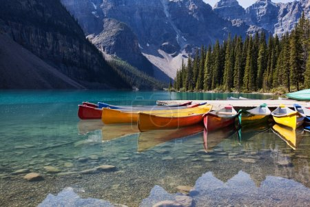 Photo for Morning light on colorful canoes along the shore of Moraine Lake, Banff National Park, Alberta, Canada. - Royalty Free Image