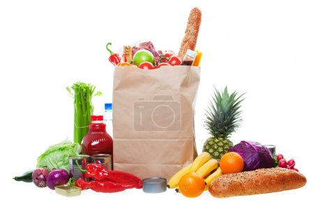 Photo for A paper bag full of groceries, surrounded by a panorama of fruits, vegetables, bread, bottled beverages, and canned goods. - Royalty Free Image