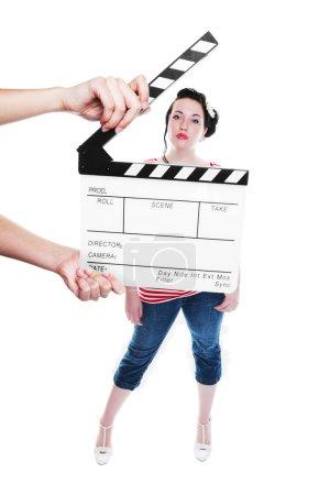 Photo pour Un panneau de battement étant tenu devant une jeune actrice vêtue de façon rockabilly. Tourné sur fond blanc. Concentrez-vous sur le clapet . - image libre de droit