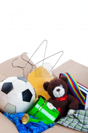 Photo for A box of unwanted stuff ready for a garage sale or to donate to a charitable organization. Generic teddy bear. Shot on white background. - Royalty Free Image