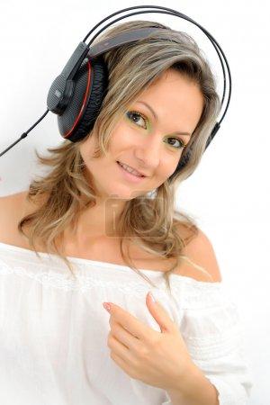 Foto de Mujer joven con auriculares en fondo blanco - Imagen libre de derechos