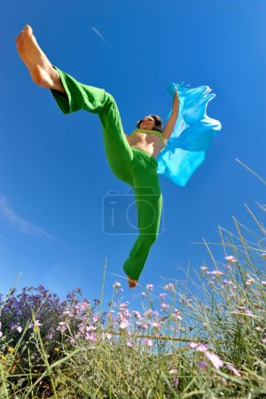 Photo for Young woman with blue scarf jumping - Royalty Free Image
