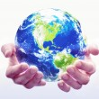 A pair of hands hold a globe with white background...