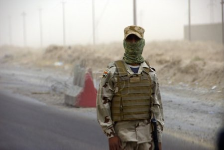 Photo for Iraqi soldier standing in road, with face covering and dust storm in background. - Royalty Free Image