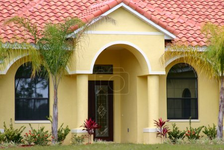 Upscale yellow Spanish-style stucco home with well...
