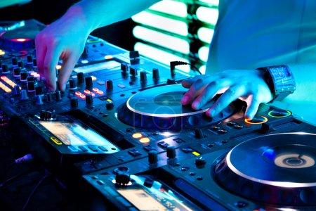 Photo pour DJ mixes la piste dans la boîte de nuit lors d'une fête - image libre de droit