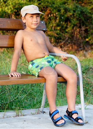 Boy smiling and sitting on bench