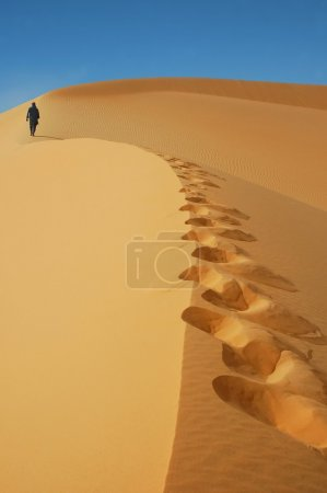 Nomad walking up a sand dune in the Sahara