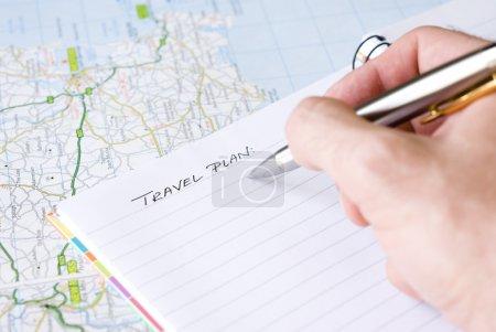 Photo pour Main qui écrit le plan de voyage dans un bloc-notes ligné spiral disposé sur une carte - image libre de droit