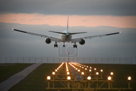 Photo for Photo of an airplane just before landing. Runway lights can be seen in the foreground. - Royalty Free Image