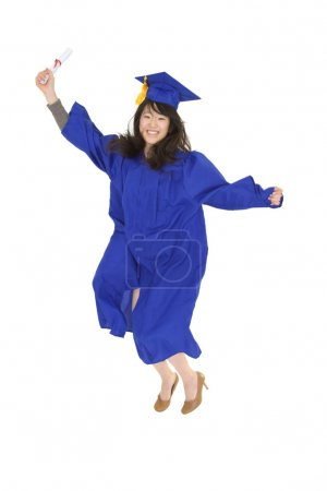 Photo for An Asian teenage in blue graduation gown and smiling and jumping in joy. She is on a white background. - Royalty Free Image