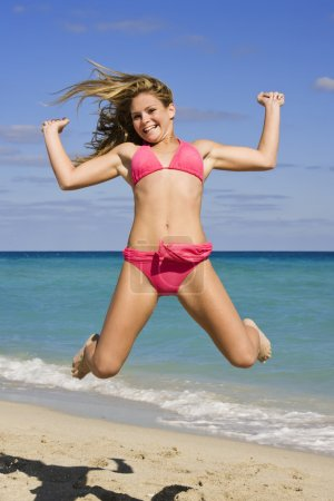 Photo pour Beautiful Caucasian female teenage having fun on South Beach jumping into the air wearing a swimsuit - image libre de droit