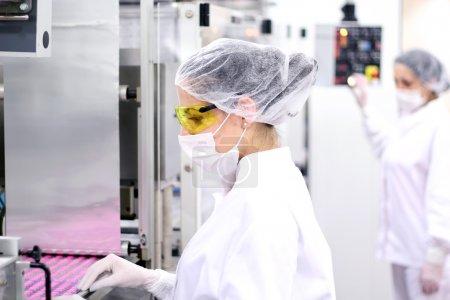 Photo pour Travailleurs pharmaceutiques surveillent le processus d'emballage de la pilule à l'usine de produits pharmaceutiques - image libre de droit