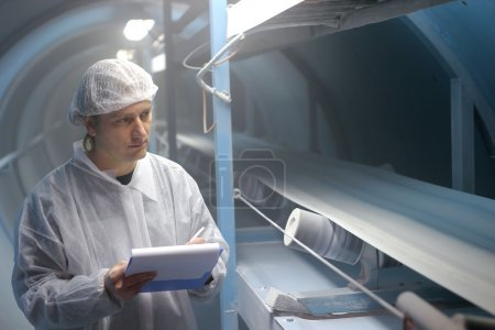 Photo for Quality inspector monitoring the process of crystal sugar production. - Royalty Free Image