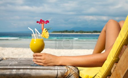 Photo pour Femme tenant un cocktail de fruits sur une plage tropicale - image libre de droit