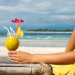 Woman holding a fruit cocktail on a tropical beach...