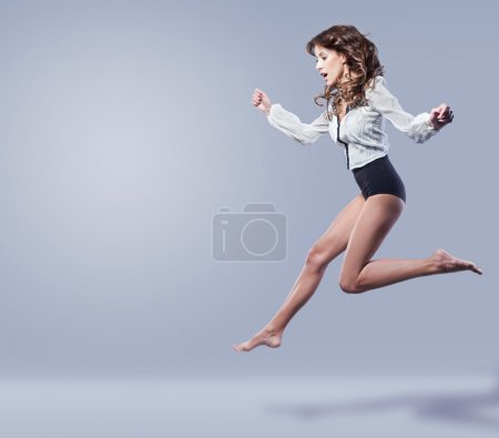 Young beautiful brunette with long legs jumping In Air on a blue background