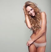 Portrait of delicate smiling woman in lingerie