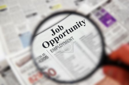 "Photo for Magnifying glass over a newspaper classified section with ""Job Opportunity"" text - Royalty Free Image"