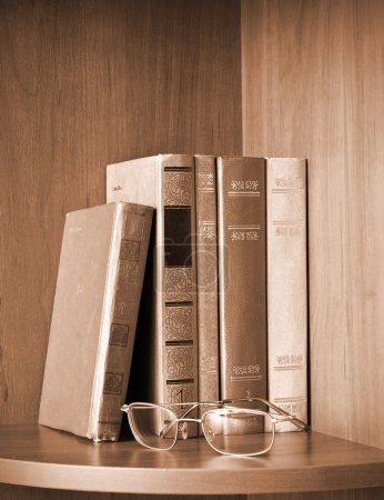 Vintage photo of old books and glasses on a shelf