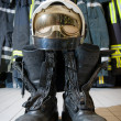 A helmet and bootz on the floor in a firestation r...