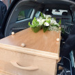 Bearers are carrying a coffin in a mourning car...