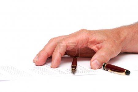 Foto de La mano en un papel con un bolígrafo, aislado sobre un fondo blanco - Imagen libre de derechos