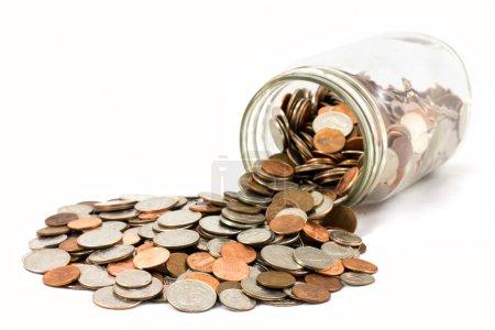 Foto de Un frasco derramado de nosotros monedas aisladas sobre un fondo blanco. - Imagen libre de derechos