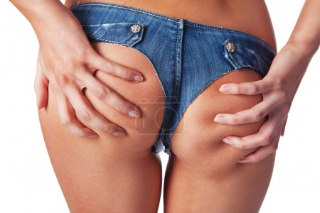 Close up of woman holding with her hands buttocks in denim short