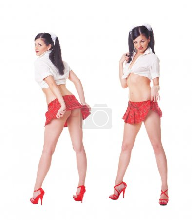 Photo for Two cute sexy schoolgirls playing with skirt, full length isolated over white background - Royalty Free Image