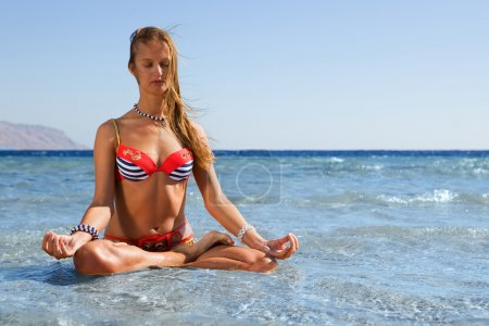 Blonde yoga woman meditating by the sea