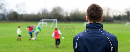 Photo for Picture of a male coaching football to children - Royalty Free Image